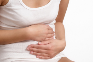 Woman with acute abdominal pain clutching her stomach with her hands as she becomes stressed by the ongoing cramps, torso view of her hands and tummy isolated on white